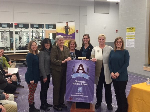 "State Board member Sarah Fowler presents CMS its ""A"" banner for top student achievement on state report card"