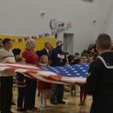 veterans and students holding unfolded flag