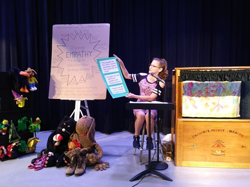 showcase picture of student on stage reading poster