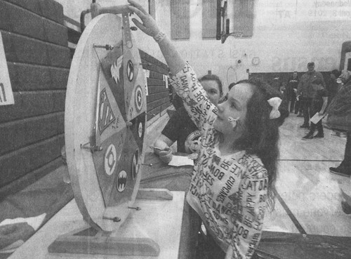 Bliss Sanders-Repko, 6, a first-grader at Cham­pion Central Elementary School, spins the wheel at the Champion Parent-Teacher Organization fundraiser held at the PK-8 school.