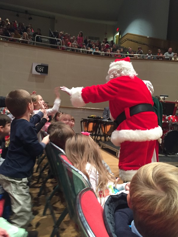 Santa high fives first graders.