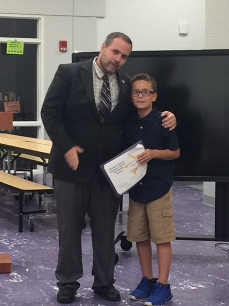 picture of board member congratulating student