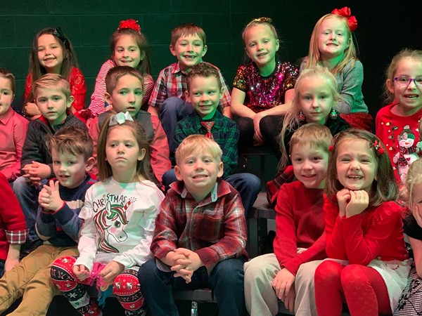 Waiting patiently for the kindergarten holiday program to begin.