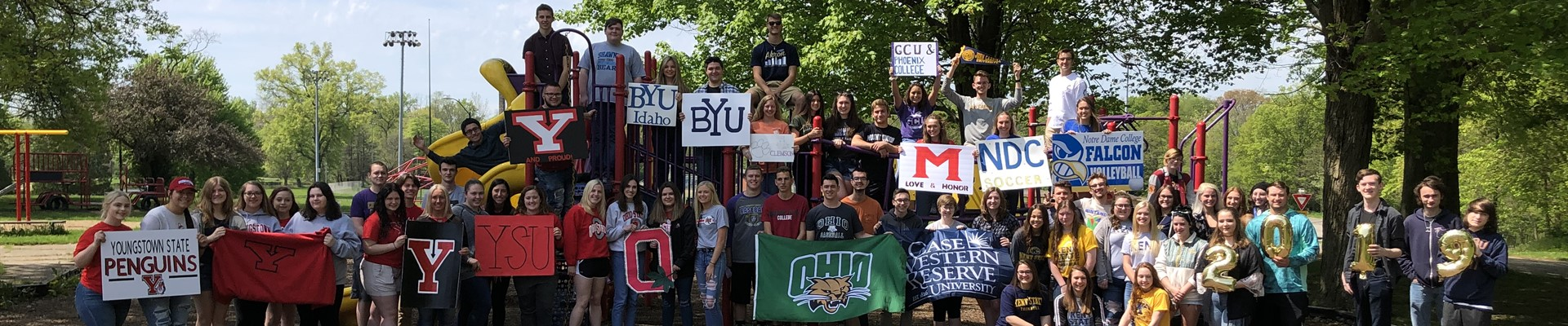 Senior class holding college signs