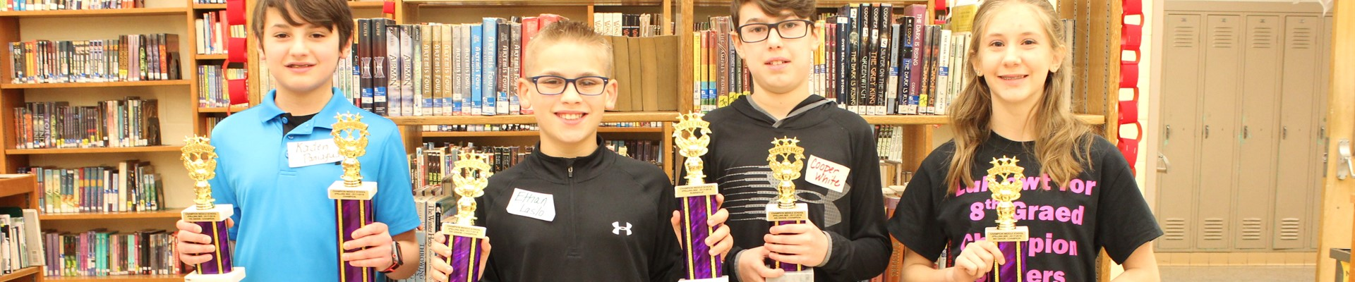 CMS Spelling Bee Winners hold trophies in library