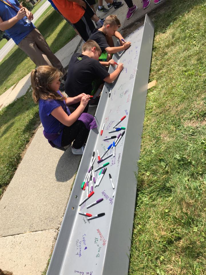 New PK-8 School Beam signing.  Students make mark in history.