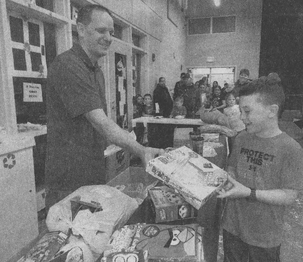 Chris Braham, 9, at rights, receives his prize from Aaron Abrahamson at the superheroes carnival.